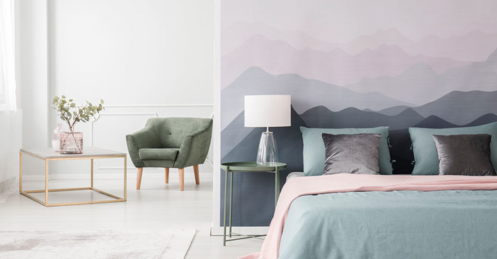 a bedroom with a blue bed and wallpaper with a mountain design