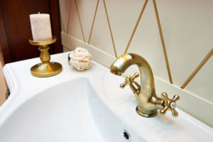 a sink with a brass faucet and a brass candle