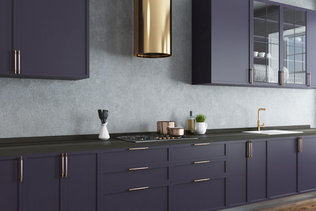 A kitchen with dark purple cabinets, a black counter top and brass accents
