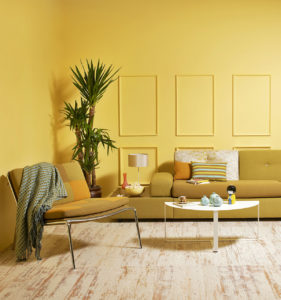 a living room with mustard colored walls, mustard colored couch and chair