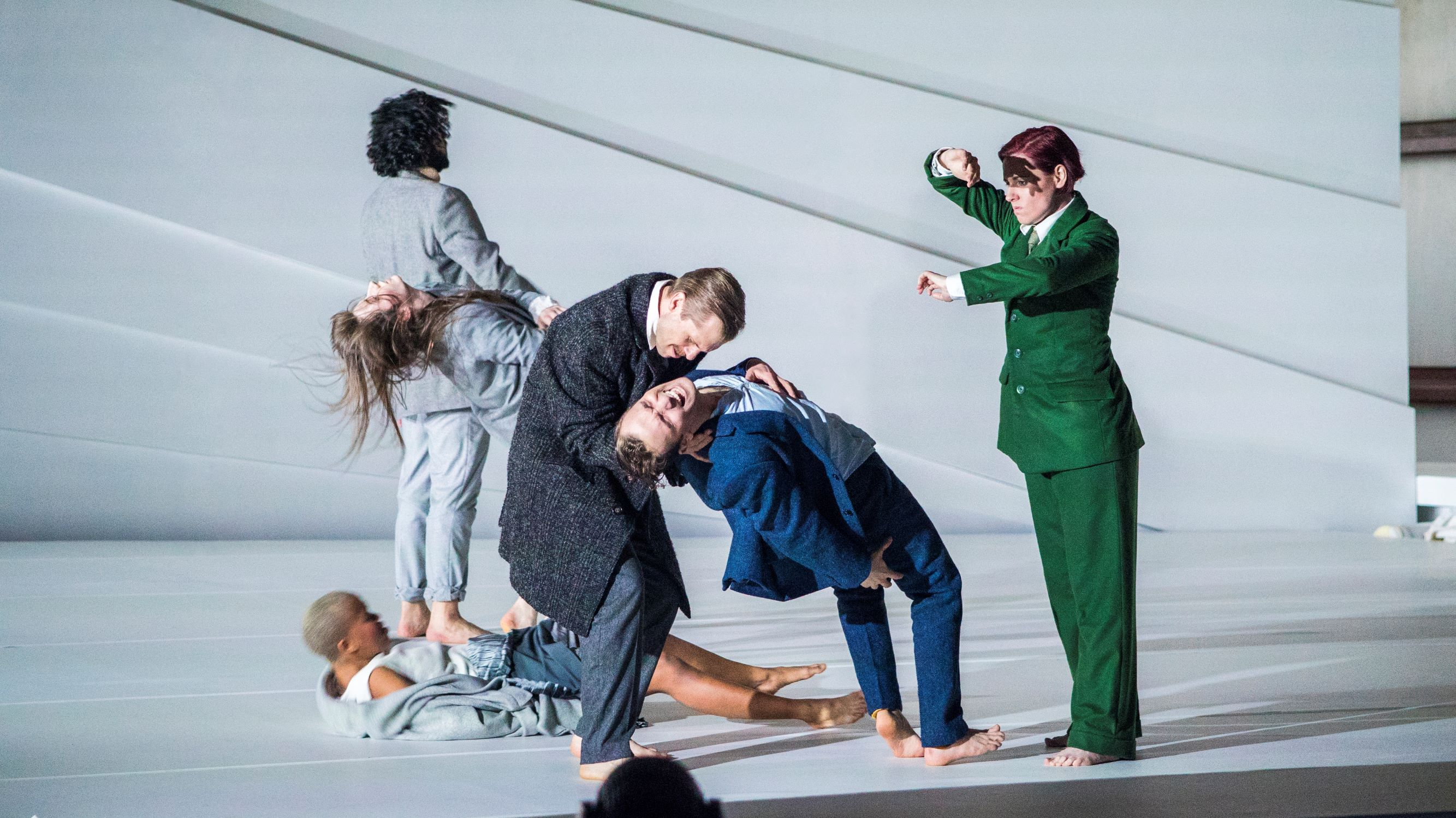 six people on a white stage. A man is falling and another man is catching him.